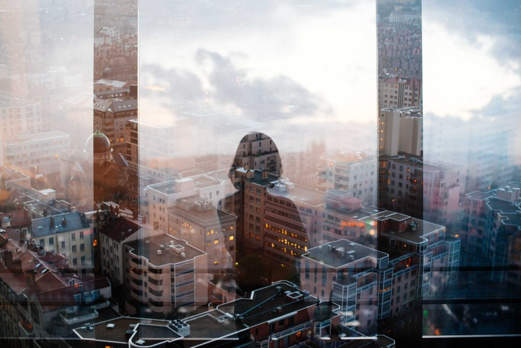 reflection of woman standing in front of glass panel facing high-rise and mid-rise buildings
